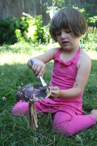 little girl painting paper mushrooms