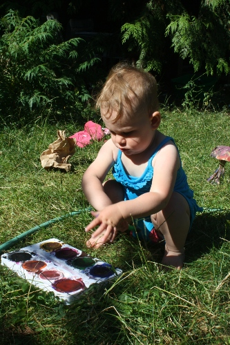 toddler playing with tempera paints
