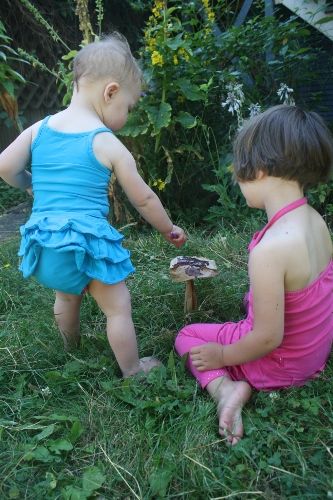 two little girls painting paper bag mushrooms