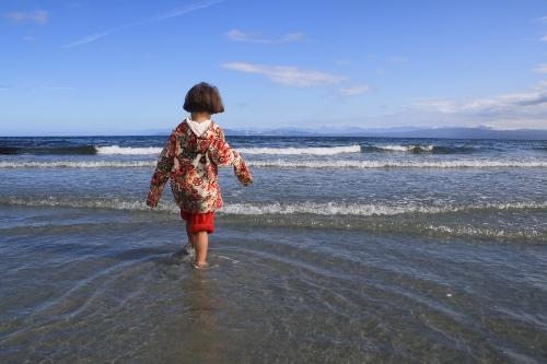 little girl walking into the ocean