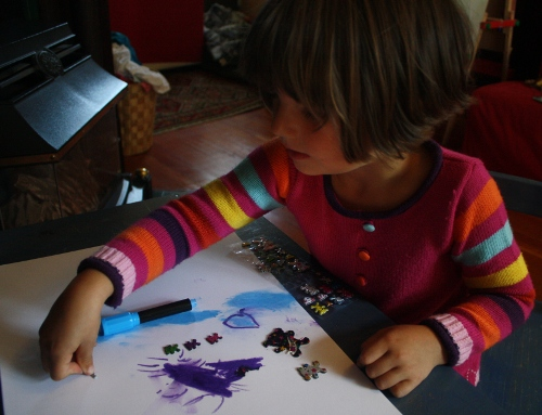preschool girl drawing with pastels and stickers