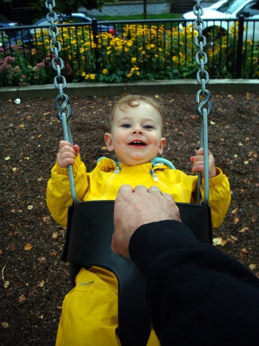 toddler wearing a rainsuit and riding in a swing