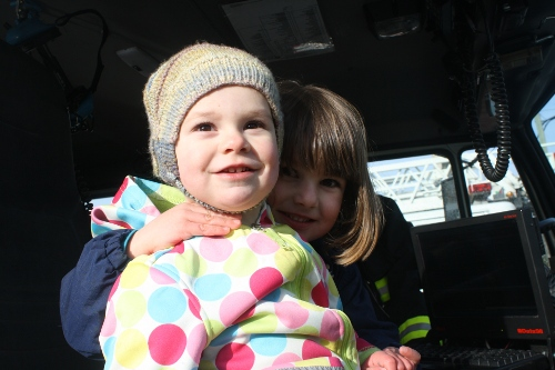 two sisters sitting in a fire truck