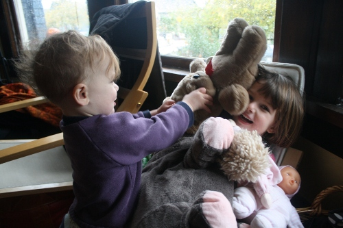 Claire piling stuffed animals on top of Bea