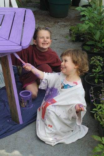 two little girls painting a patio table