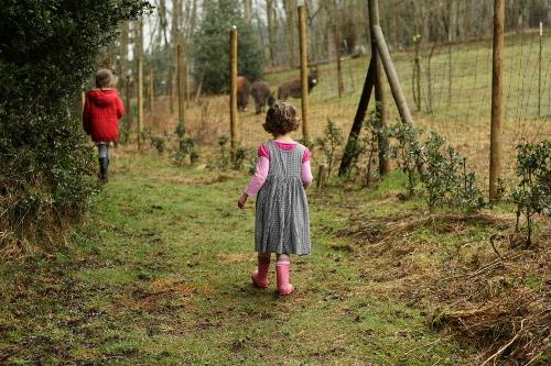 little girl walking beside a farm
