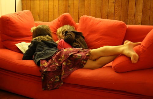 sisters reading together on the couch
